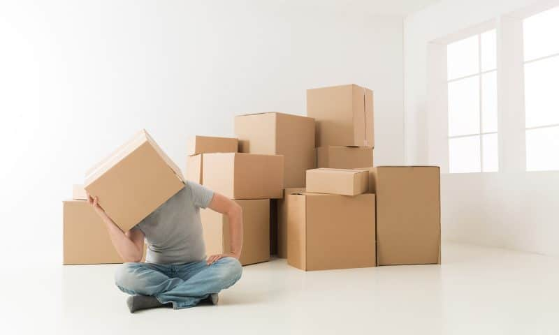 man hiding his head in cardboard box, sitting on floor in new apartment, looking worried or tired